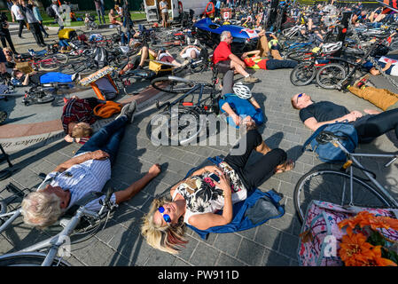 London, UK. 13th October 2018. People  take part in a ten-minute die-in by Stop Killing Cyclists outside Parliament at the end of the funeral procession behind a horse-drawn hearse to highlight the failure of governments from all the major parties to take comprehensive action on safer cycling. Stop Killing Cyclists call for £3 billion a year to be invested in a national protected cycling network and for urgent action to reduce the toxic air pollution from diesel and petrol vehicles which kills tens of thousands of people every year, and disables hundreds of thousands. After the die-in the seve - Stock Image