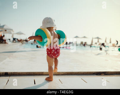 A rear view of small child with armbands walking on beach on summer holiday. - Stock Image