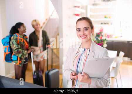Portrait confident female real estate agent helping women arriving in house rental - Stock Image
