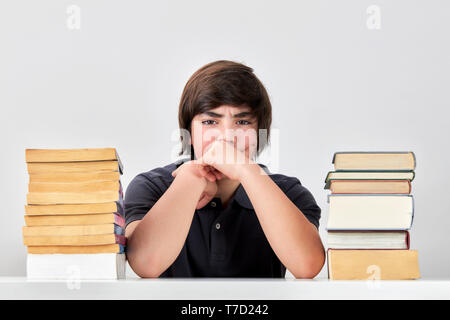 Exhausted stressed and angry teenage school boy sitting at the table between pile of books with his hands on his cheeks - Stock Image