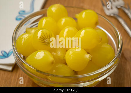 Glass bowl with traditional pickled Amsterdam silverskin onions close up - Stock Image