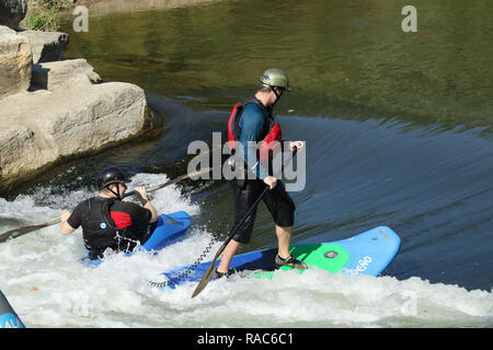 Kayaker and Standup Paddleboarder rides in a water trough. At the Whitewater feature in the Mad River. Wagner Subaru Outdoor Experience at Eastwood Me - Stock Image