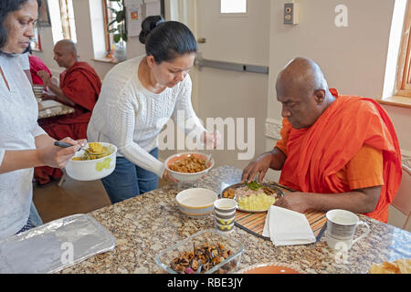 After morning services, Buddhists congregants feed their monk with homemade food. At the New York Buddhist Vihara in Queens, Village. - Stock Image