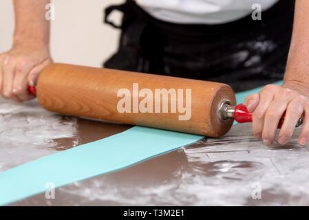 Confectioner using rolling pin preparing fondant for cake decorating . - Stock Image