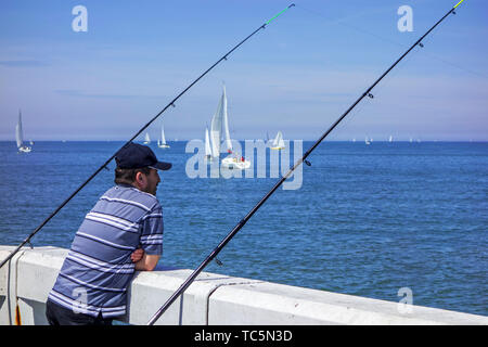 Sea angler watching sailing boats passing by from jetty along the North Sea coast in summer while fishing - Stock Image