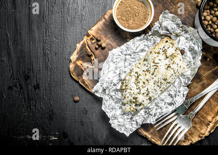 Baked chicken fillet with spices. On black background. - Stock Image
