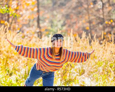 Young woman teen girl female adolescent and warm Autumn colors in nature standing on one leg pretending to fly with hands spread wide like wings - Stock Image