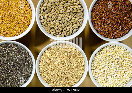 Bowl of Mixed Healthy Dry Seeds and Grains Including Linseed Sunflower Chia Pearl Barley and Quinoa - Stock Image