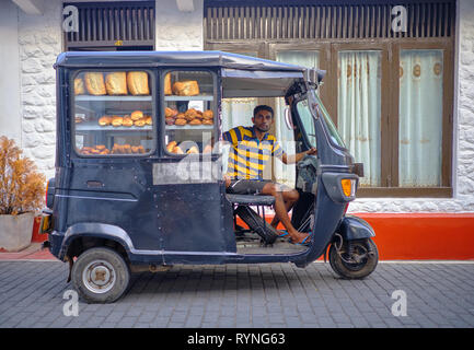 Bread delivery man in black tuktuk in the old part of Galle . Galle, Sri Lanka, January 9 2018 - Stock Image