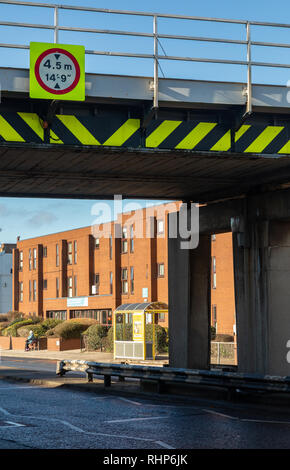 Flourescent warning sign with red circular border and black and yellow markings indicating a low railway bridge with height limit Wallasey Village Feb - Stock Image
