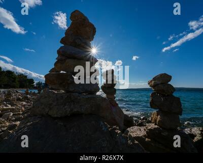 Stack of rocks on beach against bright lights silhouette rendition against peeking just emerging sun behind in background Crikvenica in Croatia - Stock Image