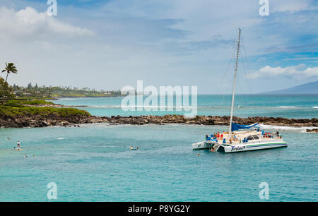 People swim and snorkel from a catamaran sailing trip off the coast of Maui. Tourist activity. - Stock Image