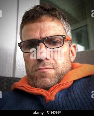 Midle aged man reading a book! - Stock Image