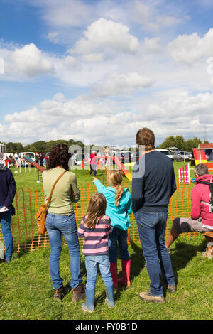 A young family watching the dog agility demonstration at the Lancashire Game and Country Festival 2015 at Scorton. - Stock Image