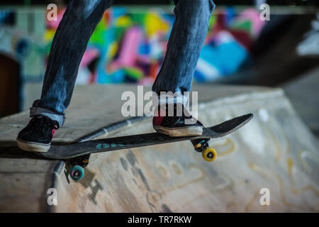 A skateboarding dropping down a ramp in the evening at a skate park - Stock Image