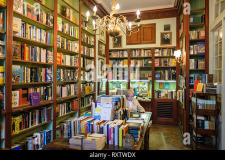 Woman reading, interior of Faulkner House Books, bookstore selling William Faulkner's books, Pirate's Alley, New Orleans French Quarter, New Orleans,  - Stock Image