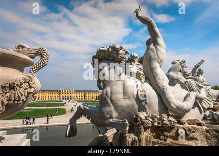 Schloss Schonbrunn, view of a triton riding a seahorse on the Neptune Fountain with the Schloss Schönbrunn palace in the distance, Vienna, Austria. - Stock Image