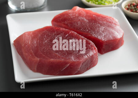 Dish with two fresh raw yellowfin tuna steaks close up - Stock Image