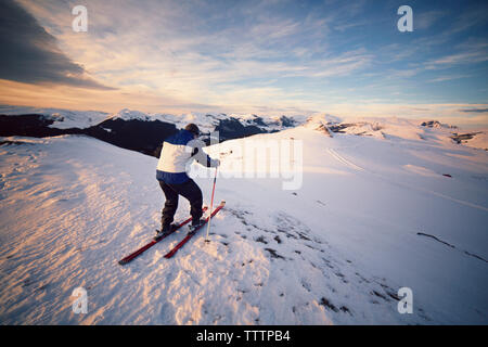 Rear view of man skiing on snowy mountain against sky - Stock Image