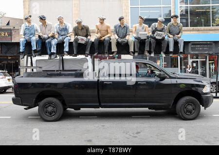 A delivery truck with a reproduction of the famous photo of construction workers eating lunch atop a skyscraper. In Astoria, Queens, New York. - Stock Image