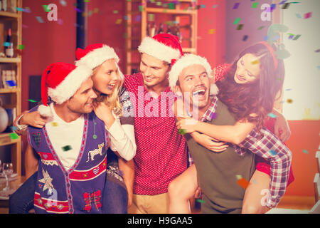 Composite image of cheerful men wearing christmas wearing giving women piggyback rides - Stock Image