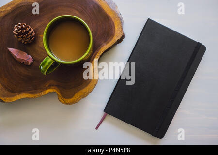 Table Top with Black Notebook and Coffee, Wood Slice, Pine Cone and Arrowhead - Stock Image