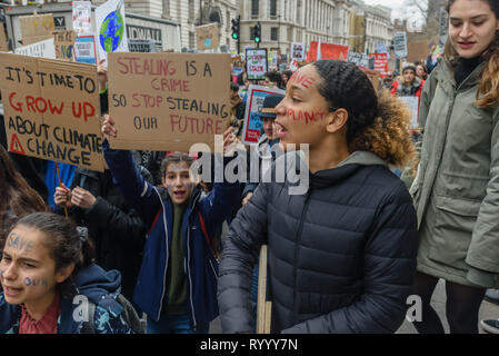 London, UK. 15th March 2019. Several thousand school students took part in the Big School Strike for the Future calling for government to take urgent action to avoid climate disaster. They met for a short rally in Parliament Square and then marched to protest outside Buckingham Palace. Police tried to stop them at the end of the Mall, but they walked around the cordon to protest on the Victoria Memorial before returning to Parliament Square. Some went on to march across Westminster Bridge and further south of the river.. Peter Marshall/Alamy Live News - Stock Image