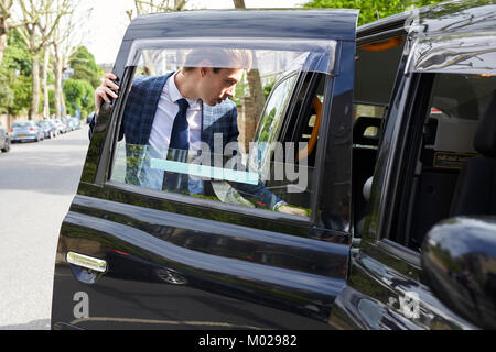 Young businessman getting into a London taxi - Stock Image