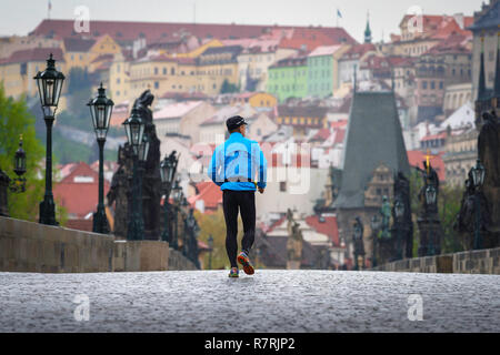 Man running jogging city alone, rear view of a middle aged man running across the Charles Bridge in Prague on an overcast day, Czech Republic. - Stock Image