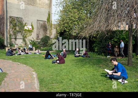 People sitting on grass in sunshine, Culpeper Community Garden, London Borough of Islington - Stock Image