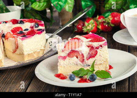 Portion of cheesecake with strawberries, blueberry and jelly on a plate - Stock Image