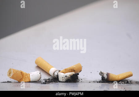 Used cigarettes discarded on metal surface with ash - Stock Image