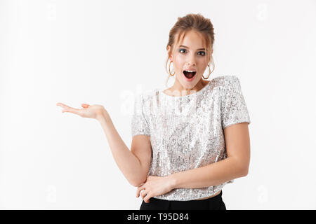 Portrait of a cheerful attractive woman wearing bright clothes and makeup standing isolated over white background, presenting copy space - Stock Image