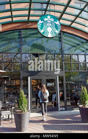 Young woman entering Starbucks Coffee shop in Park Royal Village shopping centre, West Vancouver, BC, Canada - Stock Image