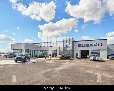 Front exterior of a Subaru new and used car dealership with a salesman and mature woman customer on the lot in Montgomery Alabama, USA. - Stock Image