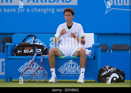 Sergiy Stakhovsky takes a break between games on a blue players bench at the Aegon International tennis tournament - Stock Image