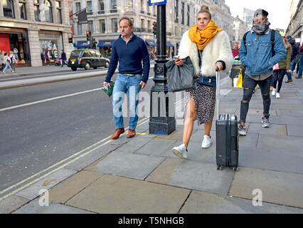 London, England, UK. Young woman in Regent Street with luggage - Stock Image