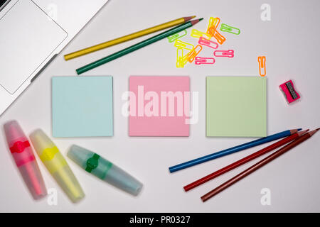 Sticky notes with markers, colored pens, paper clips laying on a table, Back to school. School and office supplies. - Stock Image