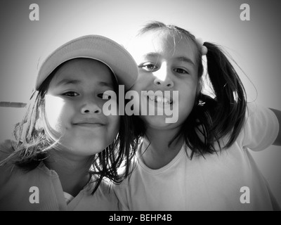 Girls sitting on baseball stands, black and white - Stock Image