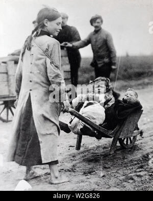 French girl using a wheelbarrow in transporting her little sister away from danger ca. 1916-1919 - Stock Image