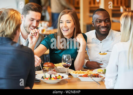 Group of friends has fun having a lunch together in the restaurant - Stock Image