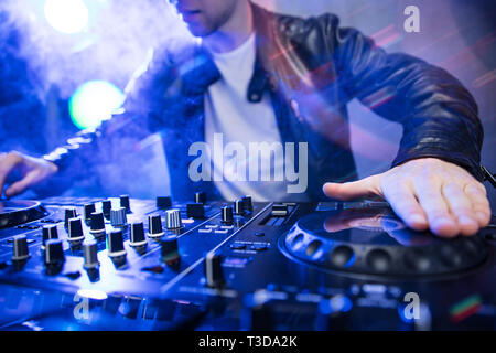 Dj mixing at party festival with red light and smoke in background - Summer nightlife view of disco club inside. Focus on hand - Stock Image