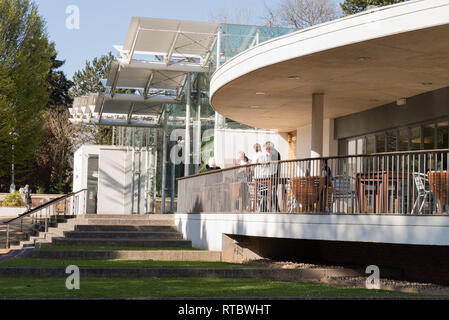 The Palm House in Jephson Gardens, Leamington Spa, England UK, exterior showing the cafe balcony with a group of people talking. - Stock Image