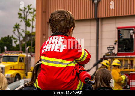 Los Angeles, California, USA 12 May 2018 A Young Fire Chief watching Los Angeles City Firefighters from Station 88 doing a demo of a car rescue on Fire Service Day. Credit: Chester Brown/Alamy Live News. - Stock Image
