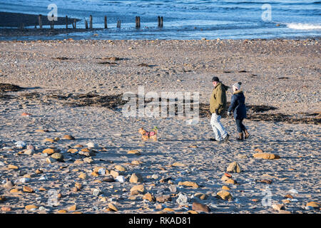Sandsend, Whitby, North Yorkshire, UK. 10th February 2019. People enjoying the last of the late evening sun on a bright but cold day on the North Yorkshire coast.  Credit: Alan Keith Beastall/Alamy Live News - Stock Image