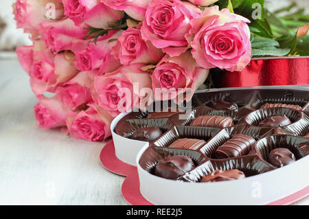 Dozen soft pink rose flowers with a heart shaped box of chocolate candy for Valentine Day over a wood background. - Stock Image