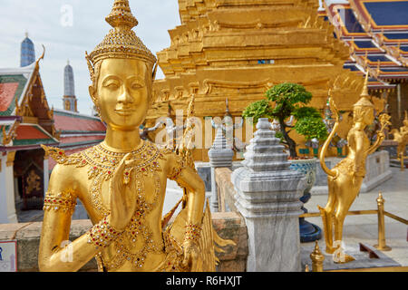 Golden dancer statues inside the Grand Palace in Bangkok, Thailand. - Stock Image
