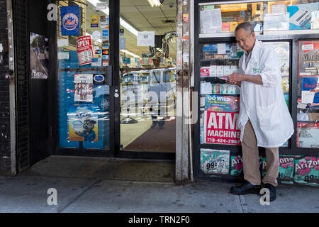 An older man checking his scratch off lottery ticket outside a small grocery store on Roosevelt Ave. under the el in Jackson heights, Queens, New York. - Stock Image