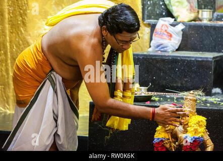 Batu Caves, Hindu Priest Performing Ceremony at Shrine to Lord Murugan, Hindu God of War, Selangor, Malaysia. - Stock Image