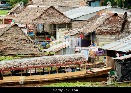 Floating houses in Iquitos, Peru. The traditional thatched roofed houses found in the poorer areas of the city. - Stock Image